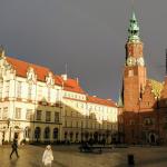 Wrocławski ratusz na tle ciemnych chmur burzowych.