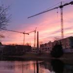 Budowa apartamentowca na tle wschodzącego słońca.